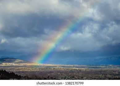 Large rainbow over fields in Spain, rural landscape seen from A1 motorway
