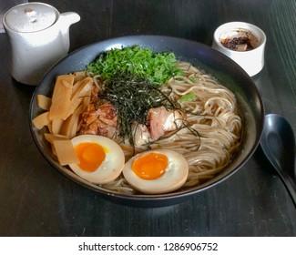 Large ramen bowl with noodles, egg, bambu, pork, green onions and nori