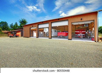 Large ranch garage with car, truck, boat and trailer in red colors. Washington, State. US