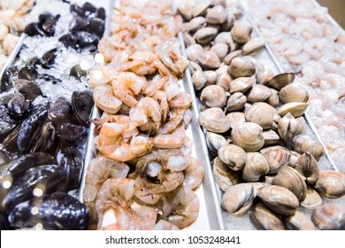 Large raw green clams shells mussels closeup shrimp crustacean prawns seafood stand on ice in fresh market behind glass on display in store, shop