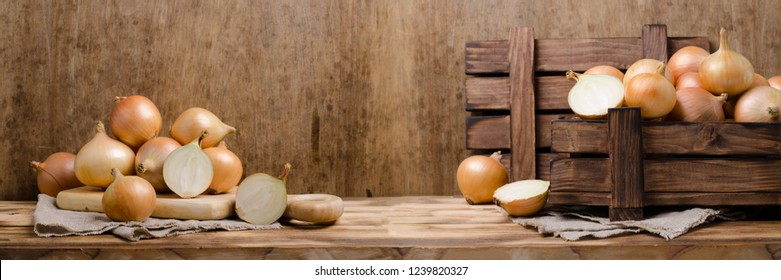 Large raw organic onions on wooden background. Selective focus.