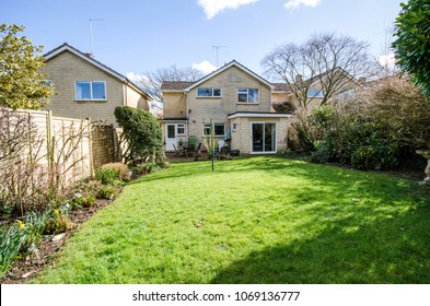 Large rear garden of a detached four bedroom house with lawn area and flowered borders. taken on a sunny spring day with blue sky