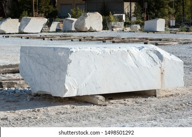 Large rectangular cut block of white Carrara marble in the forecourt of a mine or quarry resting on wooden beams in Tuscany, Italy