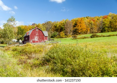 A large red barn at the bottom of a hill surrounded by a fence