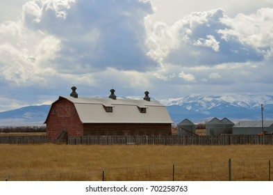 Large red barn with small silos