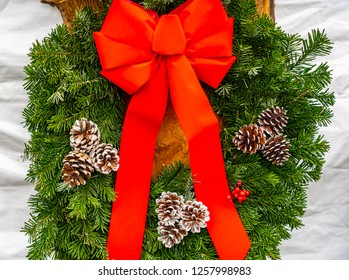 A large red bow on a green wreath with decorative pine cones.