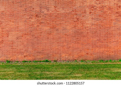 Large red brick wall background and grass