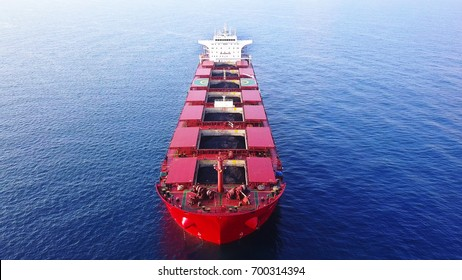Large red Bulk ship / A coal ship docking outside big power station docking with Open storage