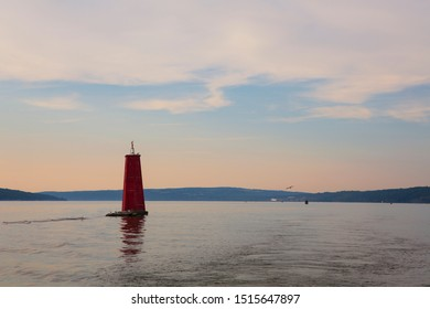 A large red buoy marks the entrance of Cayuga Inlet off Cayuga Lake, in Ithaca, New York State in the Finger Lakes Region during a calm sunset.