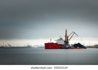 Large red cargo ship loading with a coal in the port