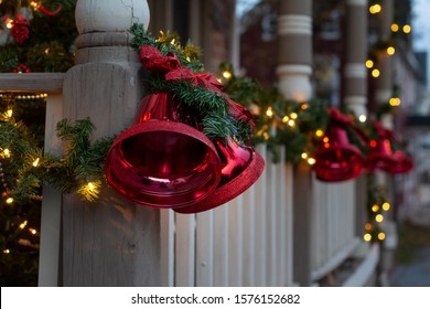 Large, red Christmas bells on front porch banister.