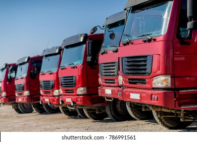 Large red dump trucks on blue sky background