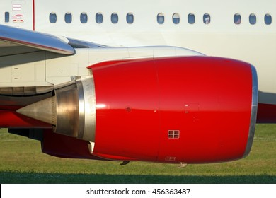 large red jet engine of heavy twin jet engine passenger plane with part fuselage engine nacelle passenger windows emergency exit door wing structure slats extended detail close up exterior side view