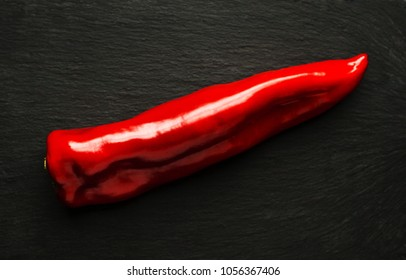 A large red pepper on black slate surface