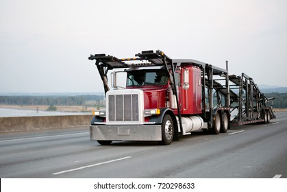 A large red powerful big rig car hauler semi truck with an empty two-tiered trailer for transporting cars is moving along the broadband scenic highway to the loading point of cars for transportation