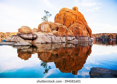 Large red rock formation with one tree in the middle of Watson Lake in Prescott, AZ, USA
