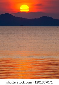 A large red setting sun over the islands of Koh Chang in eastern Thailand. Light from the sun reflects golden on the ocean.