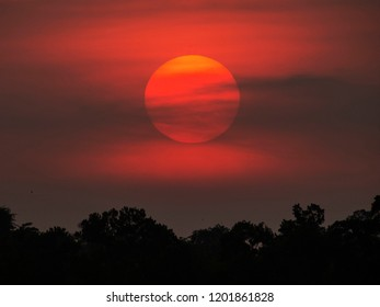 A large red setting sun over the town of Trat in eastern Thailand. The red sky glows warm as the trees are silhouetted.