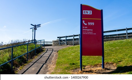 Large Red Signage with 'Call 999 in an emergency ask for Coastguard and state the above number' with blue directional signpost in the background on green grass and a blue sky.