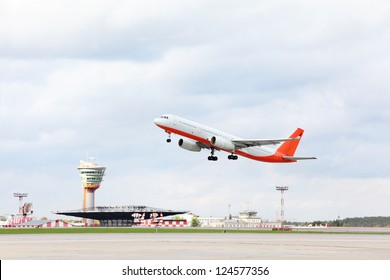 Large red and white passenger airplane takes off at airport.