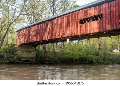 A large, red wooden bridge sits over a river in southern Indiana USA
