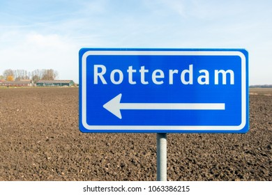 Large reflective blue sign with a white arrow in the direction of Rotterdam. The traffic sign is placed in the roadside of a country road past a recently plowed field in the Netherlands.