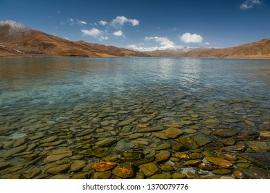 Large rocks beneath the crystal clear water of a lake in Tibet, China.