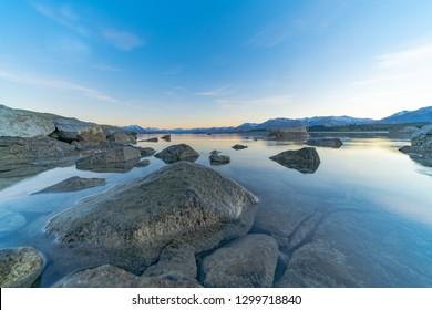 Large rocks near edge Lake Tekapo as sunsises behind distant mountains and foreshore of calm peaceful lake