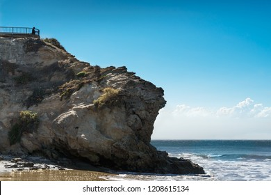Large rocky cliff overlooking the ocean, blue sky and clouds background. Fenced viewing spot at top.