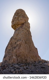 Large rocky spire with sun directly behind top of pinnacle against a blue sky.