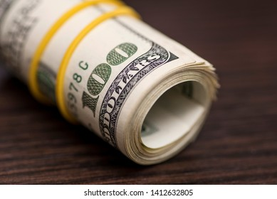 A large roll of hundred dollar bills knitted by a yellow rubber band isolated on wooden background. Roll of one hundred dollars bill on a wooden table