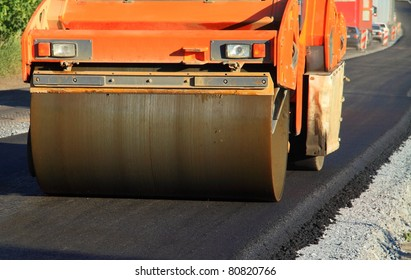 Large rolling machinery paving a road