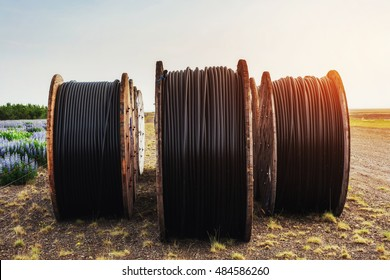 Large rolls of black wires against the blue sky at sunset.