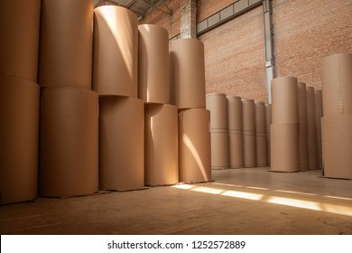 large rolls of cardboard stand in rows in stock.
