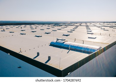 Large roof of factory with roof ventilators, drone shot from above