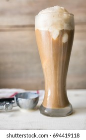Large root beer float in tall cold glass. Shown with ice cream scooper.