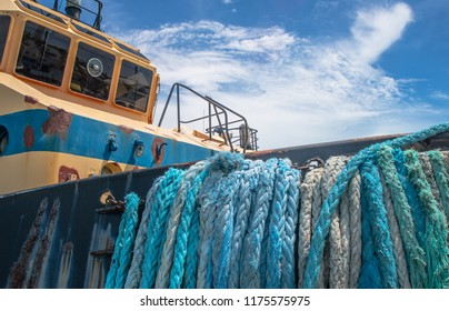 Large ropes hang over the side of an old, weathered tugboat.