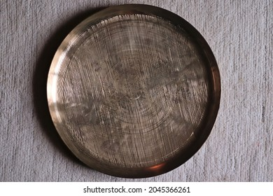 Large rough metal plate made of traditional Indian 'kansa' bronze against a textured background