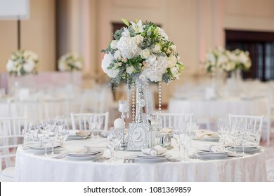 A large round arrangement of living white beautiful flowers is decorated with a festive banquet at the restaurant. Decor of the interior of the banquet hall
