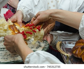 A large round braided bread is divided with female hands. It is decorated with symbolic figurines and red berries of viburnum.