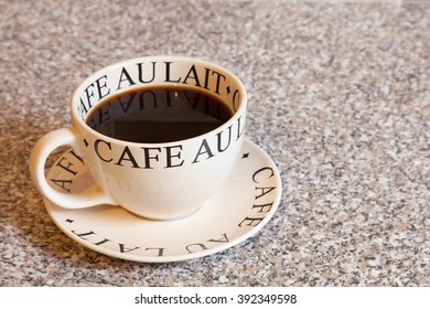 A large round cup of black coffee on a matching saucer.