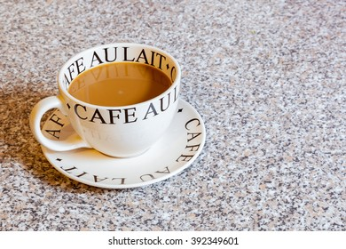 A large round cup of white coffee on a matching saucer.