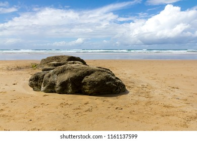 Large round rock on a sandy beach with blue sky and clouds