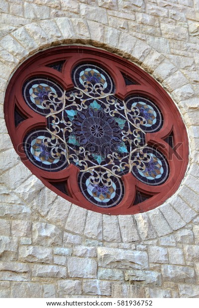 Large round stained-glass window set in old stone building