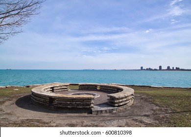 Large, round stone fire pit in Chicago city park in Chicago's south side with view of southern skyline and Indiana
