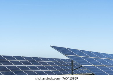 Large row of solar panels on a bright sunny day