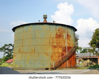 A large rusting storage tank at a vintage industrial facility