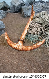 Large rusty anchor on sandy beach with rope coiled up beside it, rocks behind.