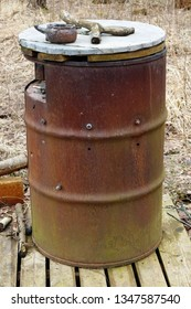 Large rusty barrel is used in the spring forest as a public cigarette ashtray.
