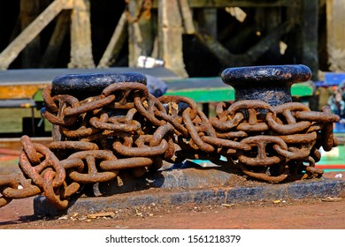 The large rusty boat anchor chain in the pile at the harbor.